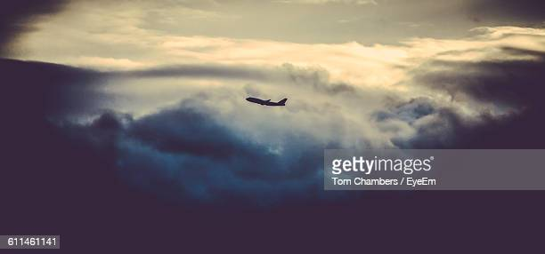 Silhouette Airplane Flying Against Cloudy Sky