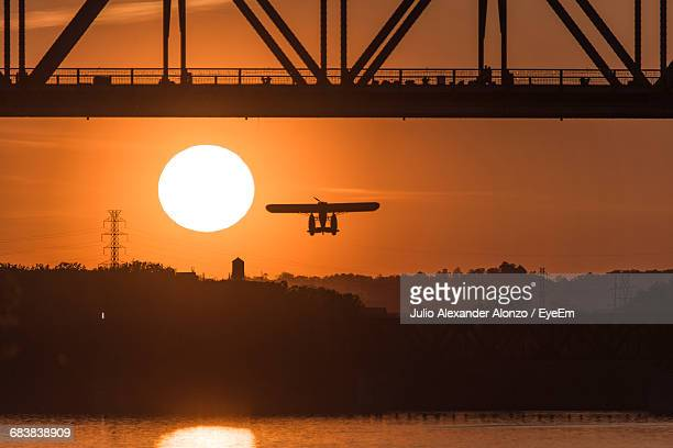 Silhouette Airplane Flying By George Rogers Clark Memorial Bridge Over Ohio River Against Sky During Sunset