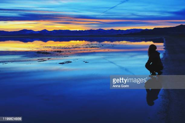 silhouette and reflection of young woman crouching at edge of lake and looking at view at sunset with mountains on horizon, bonneville salt flats, utah - bonneville salt flats stock pictures, royalty-free photos & images