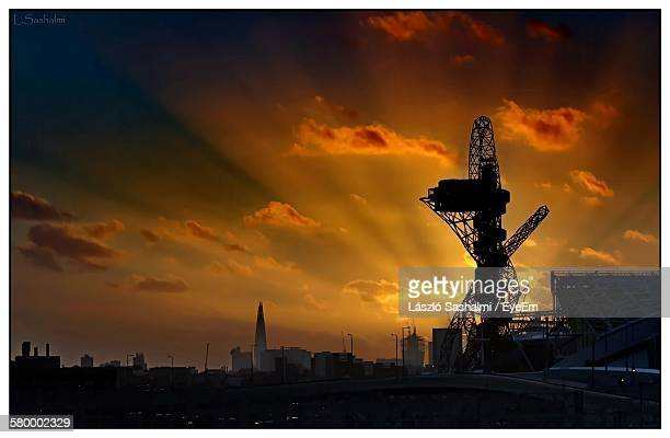 silhouette arcelormittal orbit against sunset sky at olympic park - stratford london stock pictures, royalty-free photos & images