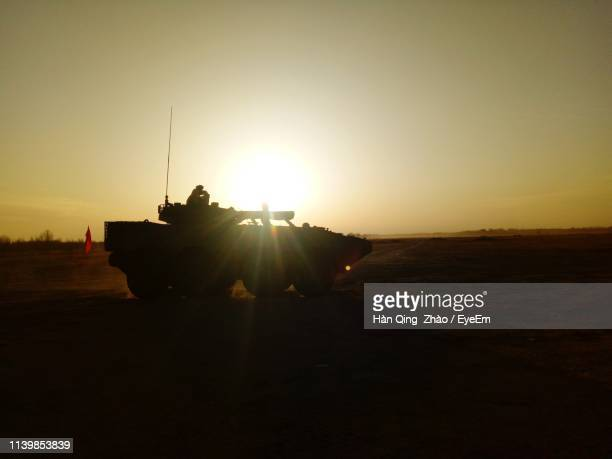 silhouette armored tank on land against sky during sunset - armored vehicle stock pictures, royalty-free photos & images
