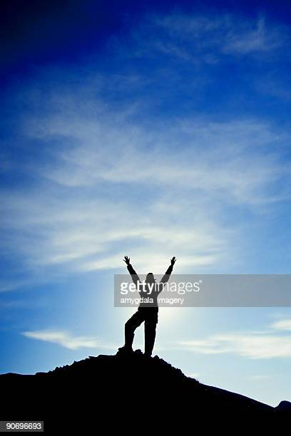 silhouette arms raised into sky landscape