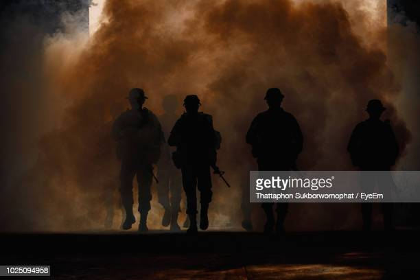 silhouette army soldiers amidst smoke at sunset - konflikt stock-fotos und bilder