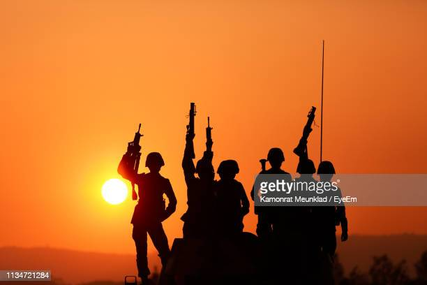 silhouette army soldiers guns celebrating against orange sky - army soldier stock pictures, royalty-free photos & images