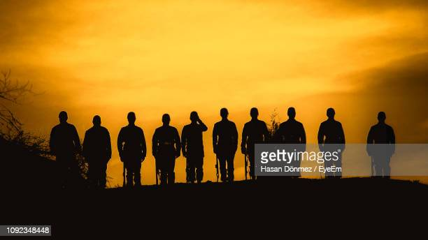 silhouette army soldiers standing in row against sky during sunset - arrangement stock pictures, royalty-free photos & images