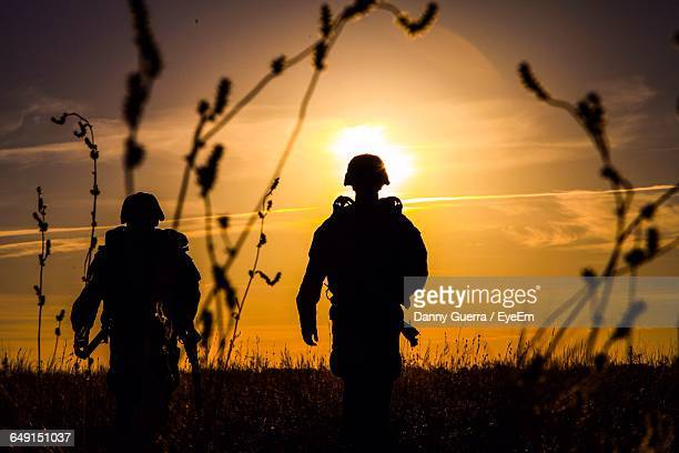 silhouette army soldiers standing on field during sunset - army soldier stock photos and pictures