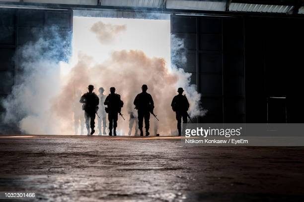silhouette army soldiers walking by tear gas walking on floor - riot stock pictures, royalty-free photos & images
