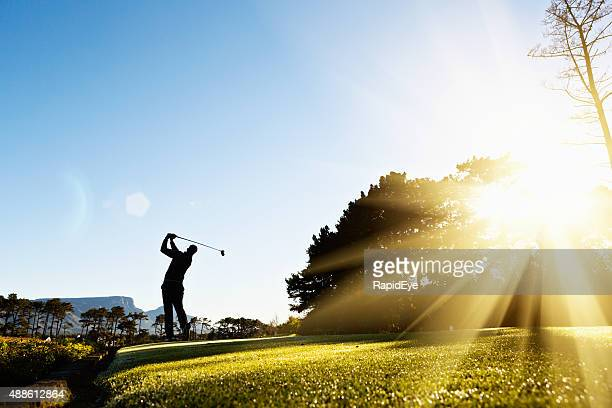 silhouette as young golfer swings on beautiful, sunlit course - golf swing stock pictures, royalty-free photos & images