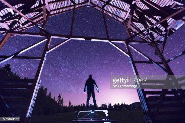 A silhouette at the entrance to a barn on a starry night, Fintry Provincial Park, British Columbia, Canada