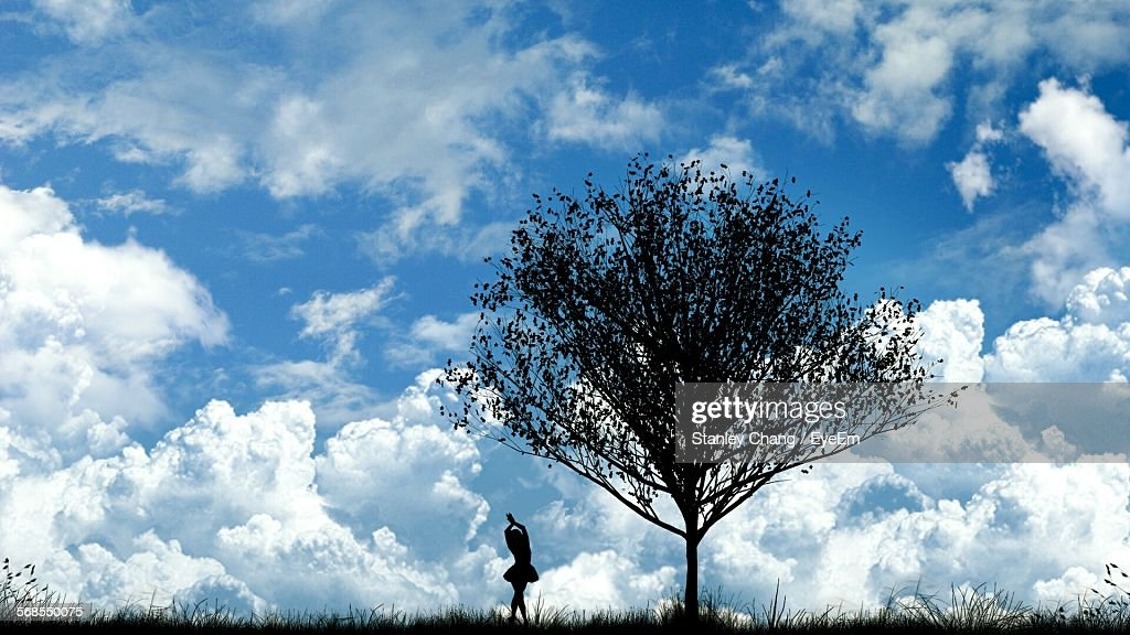 Silhouette Ballet Dancer Under Tree Against Cloudy Sky : Stock Photo