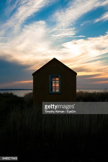 Silhouette Beach Hut Against Sky During Sunset