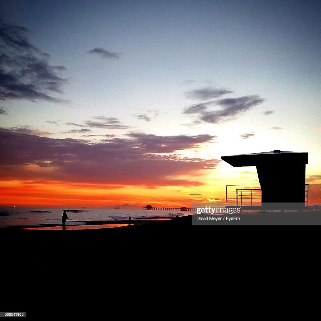 Silhouette Beach Hut On Sea Shore Against Cloudy Sky During Sunset : Stock Photo