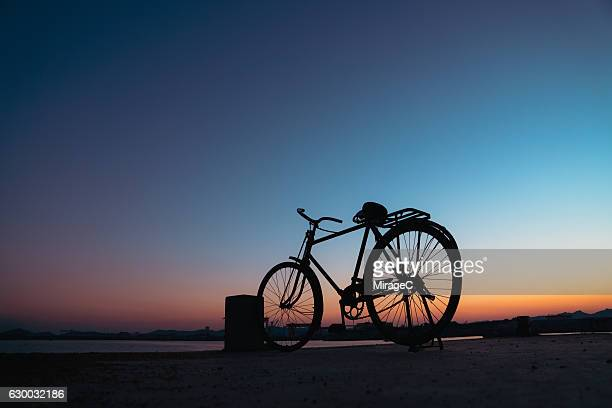 Silhouette Bicycle On Dock Against Colorful Sky