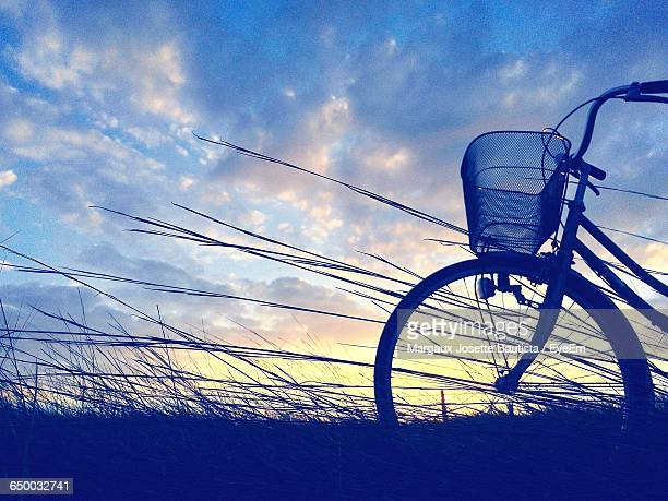 silhouette bicycle on field against sky during sunset - margaux stockfoto's en -beelden