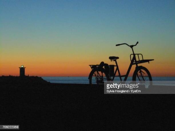 Silhouette Bicycle Parked By Sea Against Sky During Sunset
