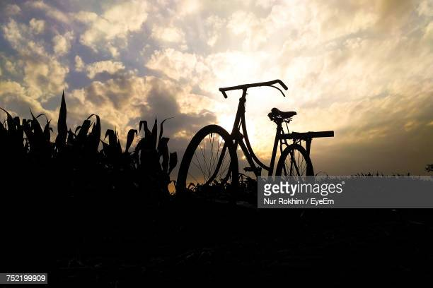 Silhouette Bicycles On Field Against Sky