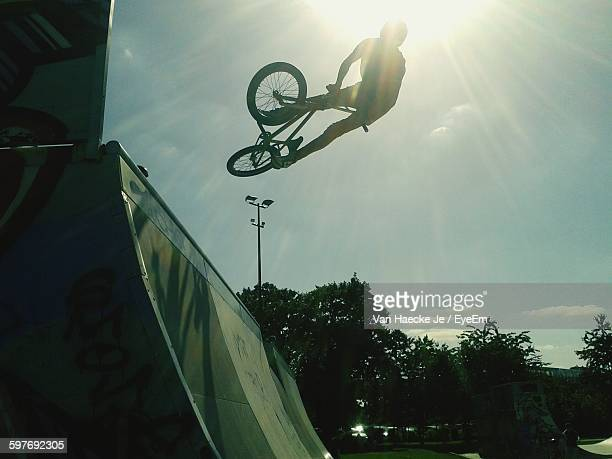 Silhouette Bmx Rider Performing Stunt Against Sky