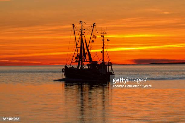 silhouette boat in sea against orange sky - husum stock-fotos und bilder