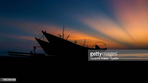 Silhouette Boat On Beach Against Sky During Sunset