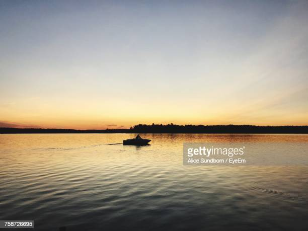 silhouette boat sailing in lake against sky during sunset - st. albans stock pictures, royalty-free photos & images