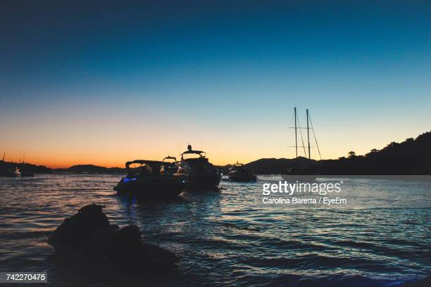 Silhouette Boat Sailing In Sea Against Clear Sky During Sunset