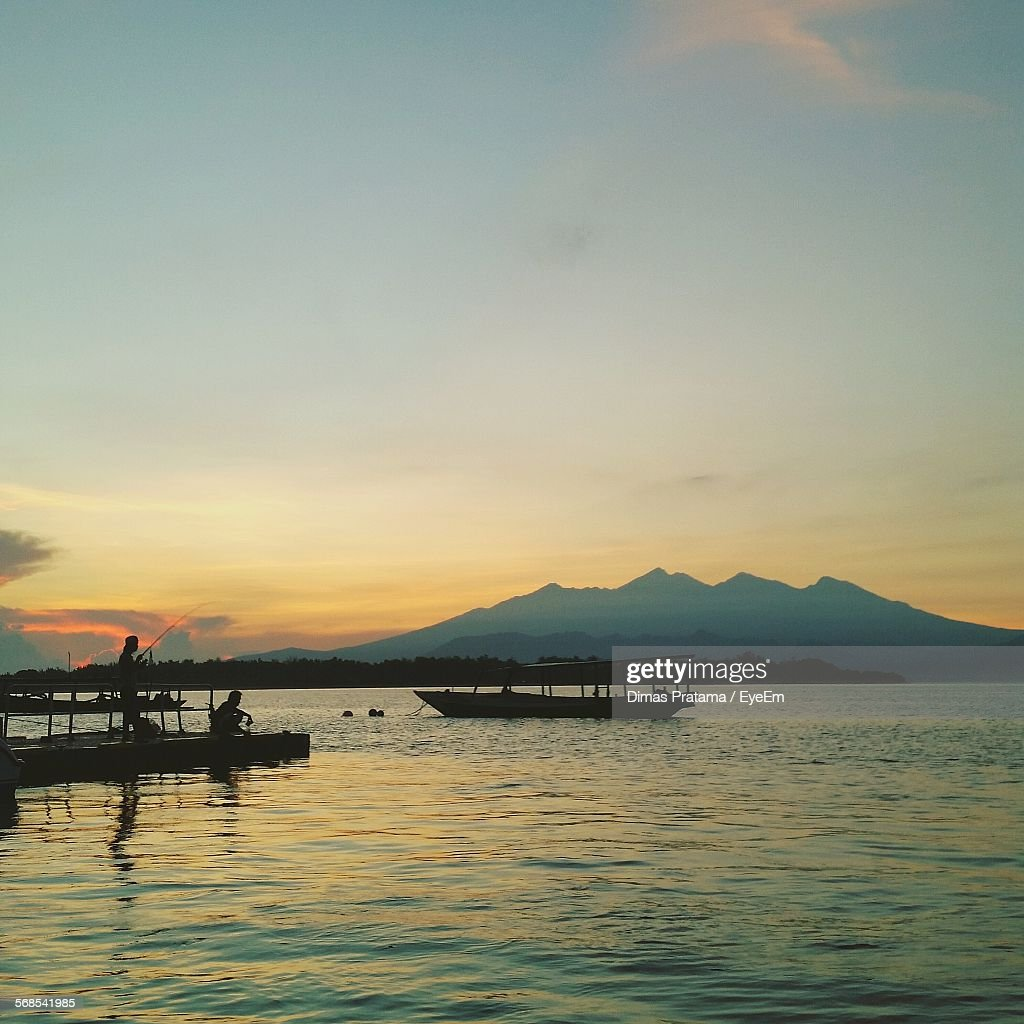 Silhouette Boat Sailing In Sea In Front Of Mountains Against Sky At Dusk : Stock Photo