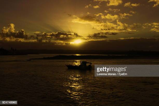 silhouette boat sailing on sea against sky during sunset - lorenna morais - fotografias e filmes do acervo