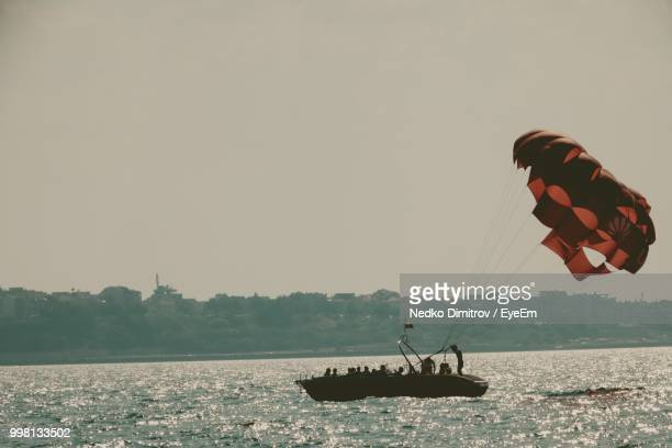 Silhouette Boat With Parachute Over Sea Against Clear Sky