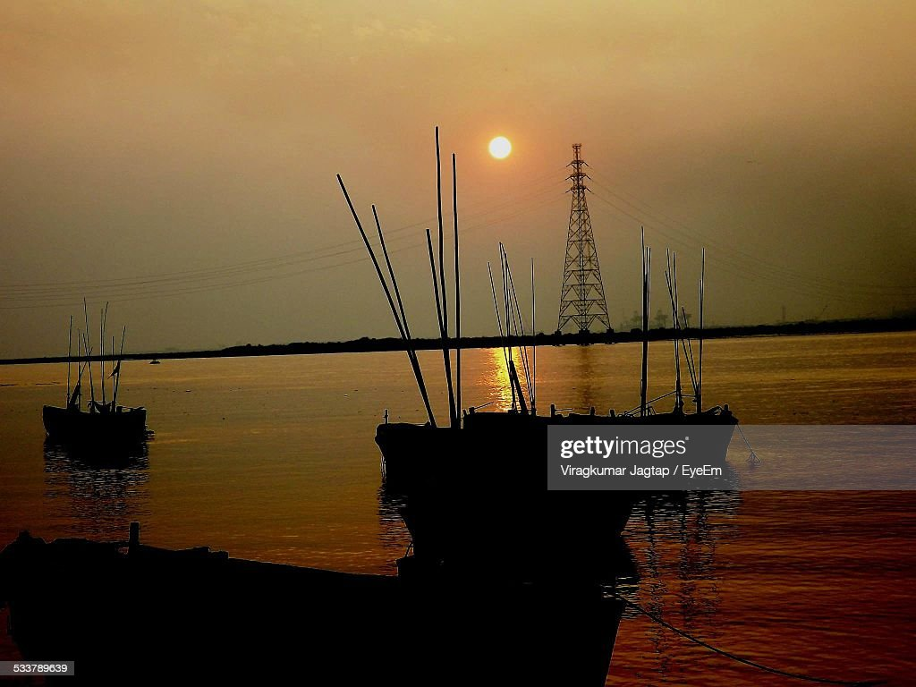 Silhouette Boats And Electricity Pylon Against Sky During Sunset : Foto stock