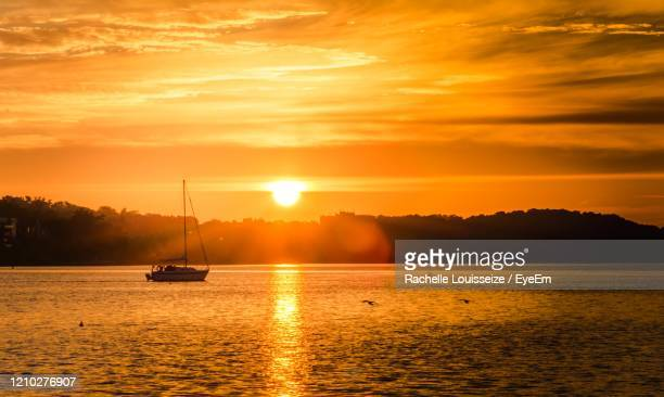 silhouette boats in sea against orange sky - barrie stock pictures, royalty-free photos & images