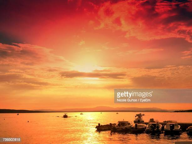 Silhouette Boats In Sea Against Orange Sky