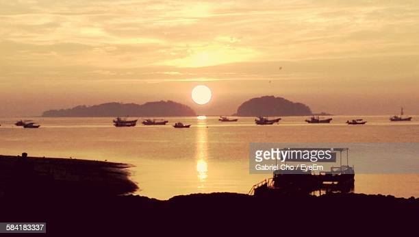 Silhouette Boats In Sea Against Sky During Sunrise