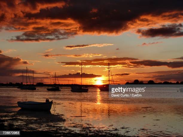Silhouette Boats Moored On Sea Against Orange Sky