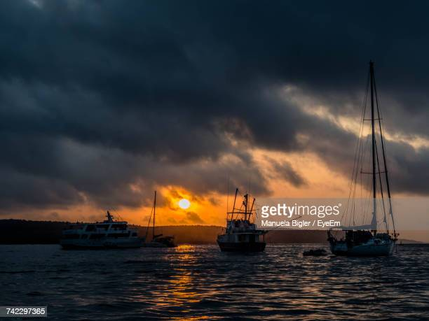 Silhouette Boats Sailing On Sea Against Sky During Sunset
