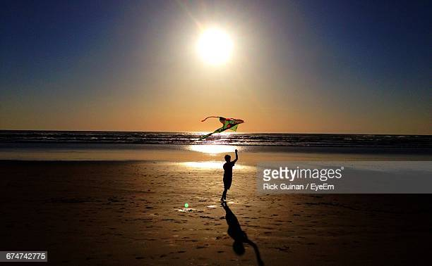Silhouette Boy Flying Kite At Beach Against Sky During Sunset