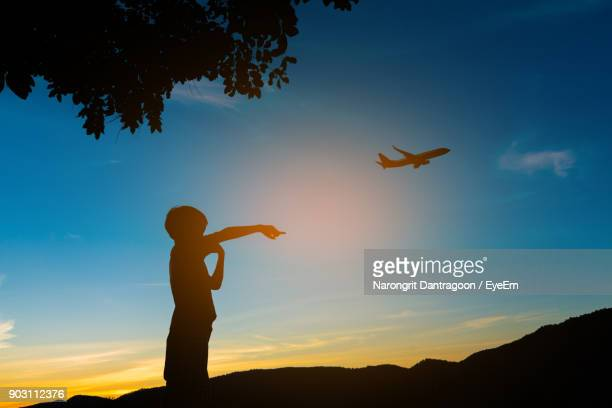 Silhouette Boy Gesturing While Air Plane Flying Against Sky