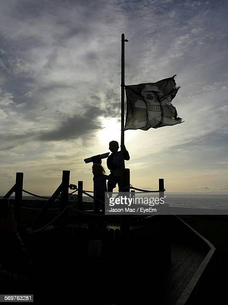 Silhouette Boy Holding Pirate Flag By Sea At Sunset