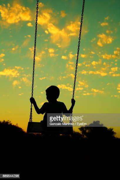 Silhouette Boy On Swing At Playground Against Sky During Sunset