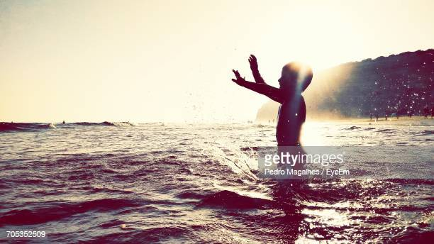 Silhouette Boy Playing In Sea Against Clear Sky During Sunset