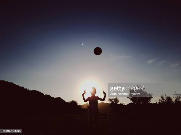 Silhouette Boy Playing With Ball Against Sky During Sunset