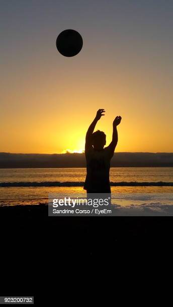 Silhouette Boy Playing With Ball At Beach Against Sky During Sunset