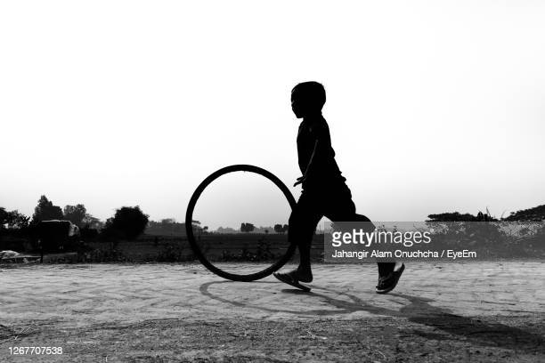 silhouette boy playing with tire on land against clear sky - savar stock pictures, royalty-free photos & images