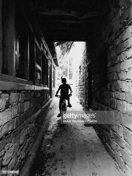 silhouette boy riding bicycle at alley - india reynolds - fotografias e filmes do acervo