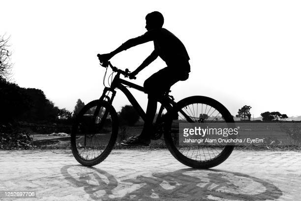 silhouette boy riding bicycle on street - savar stock pictures, royalty-free photos & images