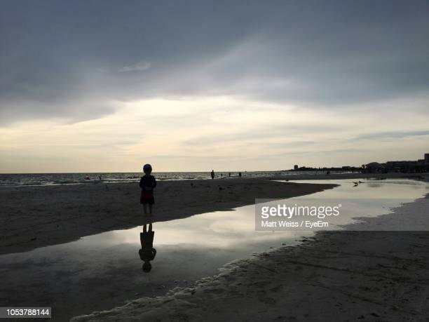 silhouette boy standing at beach against cloudy sky - siesta key bildbanksfoton och bilder