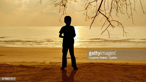 Silhouette Boy Standing At Beach During Sunset