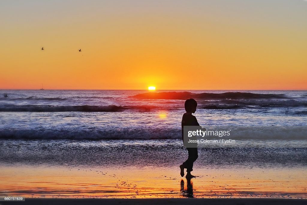 Silhouette Boy Walking At Beach Against Sky During Sunset : Stock Photo