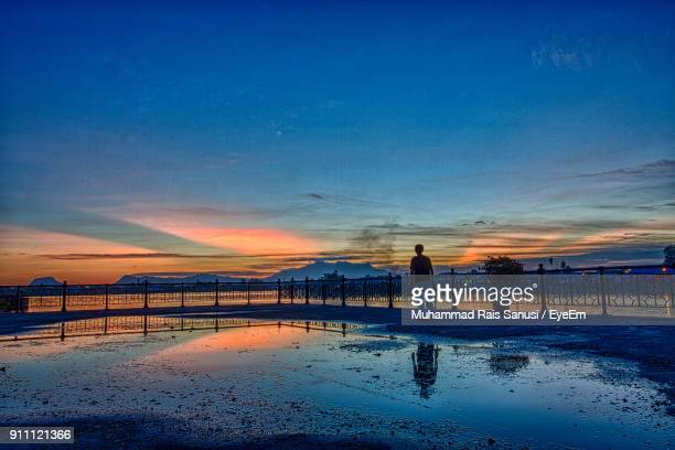 silhouette boy walking on beach pier sky during sunset - sarawak state stock pictures, royalty-free photos & images