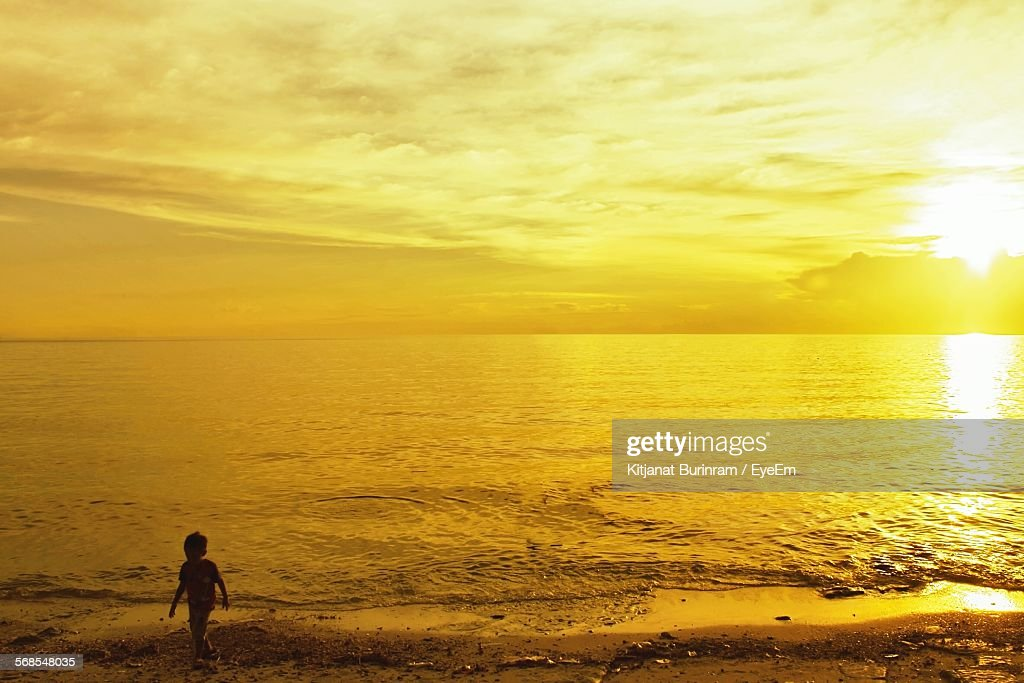 Silhouette Boy Walking On Shore Against Yellow Sunset Sky : Stock Photo