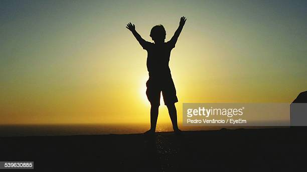 Silhouette Boy With Arms Raised In Front Of Sea Against Sky During Sunset